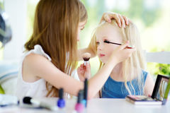 Two cute funny sisters applying make-up on sunny summer day at home. Adorable girls playing with their mommy`s cosmetic accessories Stock Image