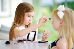 Two cute funny sisters applying make-up on sunny summer day at home. Adorable girls playing with their mommy`s cosmetic accessories Royalty Free Stock Photos