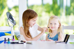 Two cute funny sisters applying make-up on sunny summer day at home. Adorable girls playing with their mommy`s cosmetic accessories Royalty Free Stock Photo