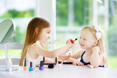Two cute funny sisters applying make-up on sunny summer day at home. Adorable girls playing with their mommy`s cosmetic accessories Royalty Free Stock Photography