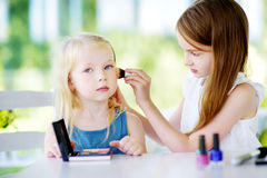 Two cute funny sisters applying make-up on sunny summer day at home. Adorable girls playing with their mommy`s cosmetic accessories Stock Images