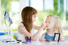 Two cute funny sisters applying make-up on sunny summer day at home. Adorable girls playing with their mommy`s cosmetic accessories Royalty Free Stock Images
