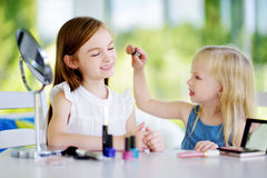 Two cute funny sisters applying make-up on sunny summer day at home. Adorable girls playing with their mommy`s cosmetic accessories Stock Photos