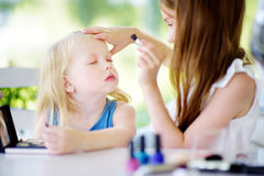 Two cute funny sisters applying make-up on sunny summer day at home Royalty Free Stock Photography