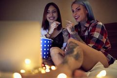 Two cute gay girls with tattoos watching a movie