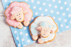 Two cute gingerbread sheep on blue polka dot background Royalty Free Stock Images