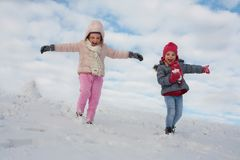 Two cute girl in the snow. stock photos