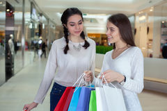 Two cute girl walks in the mall with gift bags looking into. Surprise from what he saw Stock Photos