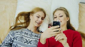 Two cute girlfriends rest on the bed and talk on the phone. Top view stock video