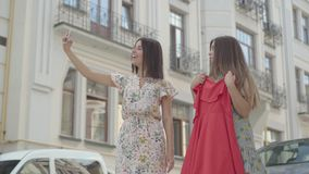 Two cute girlfriends after shopping with shopping bags taking selfie on cellphone with new dress outdoors. Leisure of. Two happy girlfriends after shopping with stock footage