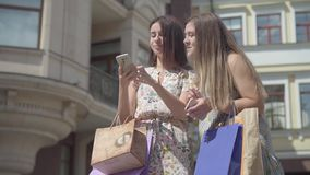 Two cute girlfriends after shopping with shopping bags taking selfie on cellphone outdoors. Leisure of happy girls. Two happy girlfriends after shopping with stock footage