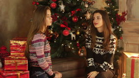 Two cute girlfriends sit by the Christmas tree and laughing. Two cute girlfriends sit by the Christmas tree, talking and laughing stock footage
