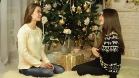 Two cute girlfriends sit near a Christmas tree stock footage