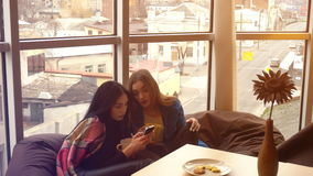 Two cute girlfriends sitting in chairs, look into the phone. And something to discuss stock video