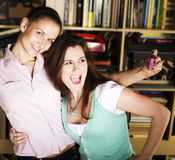 Two cute girlfriends taking photo of themselves in library, lifestyle people concept Stock Photos