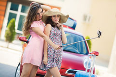 Two cute girlfriends taking selfies near the car Royalty Free Stock Image