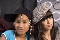 Two cute girls. Two cute teenagers, one african america the other caucasian wearing hats Stock Photo