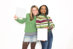 Two cute girls. /teens holding blank signs in a studio setting royalty free stock image