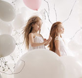Two cute girls among the balloons Royalty Free Stock Photos