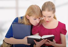 Two cute girls college reading book. Two cute girls college enthusiastically read the book royalty free stock images