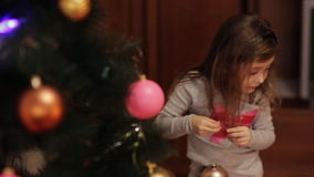 Two cute girls decorating Christmas tree. New year preparation. Girls having fun. Little girls in comfortable home clothes sitting on floor in beautiful stock footage