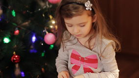 Two cute girls decorating Christmas tree. New year preparation. Girls having fun. Little girls in comfortable home clothes sitting on floor in beautiful stock video