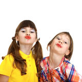 Two cute girls demonstrate painted lips. Two cute girls with crooked wrong makeup demonstrate painted lips isolated on white background Stock Photo