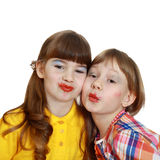 Two cute girls demonstrate painted lips. Two cute girls with crooked wrong makeup demonstrate painted lips isolated on white background Royalty Free Stock Photos