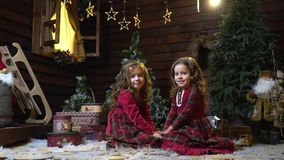 Two little girls in dresses are sitting in the middle of the room with New Year`s decorations, there are presents around. Two cute girls in dresses smiling and stock footage