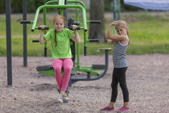 Two cute girls on the equipment for exercise in the Park. Sport. Royalty Free Stock Images