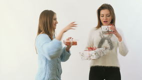 Two cute girls gives presents to each other at white background. Two pretty girlfriends with festive gifts dances at white background. Charming girls gives stock footage