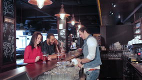 Two cute girls and a guy get his order from the. Cheerful company of guys and girl celebrating at the bar. The company has a rest after work. Cheerful company stock video
