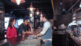Two cute girls and a guy make an order to the. Cheerful company of guys and girl celebrating at the bar. The company has a rest after work. Cheerful company stock video