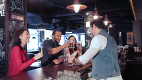 Two cute girls and a guy relaxing in a bar. Cheerful company of guys and girl celebrating at the bar. The company has a rest after work. Cheerful company relax stock footage