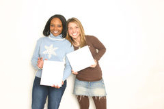 Two cute girls holding blank signs. Shot in a studio setting royalty free stock photography