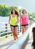 Two cute girls jogging outdoors Stock Photos