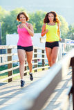 Two cute girls jogging outdoors Royalty Free Stock Photos