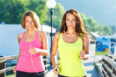 Two cute girls jogging outdoors Stock Photo