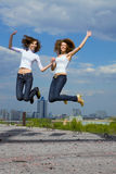 Two cute girls jumping and having fun. On the city Stock Photos