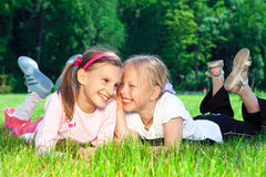 Two cute girls laughing on the grass Stock Photo