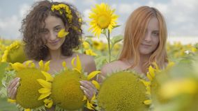 Two cute girls looking at the camera smiling standing in the sunflower field covering bodies with sunflowers. Bright