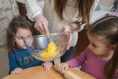 Two cute girls looking how mother mixing egg yolk in bowl Royalty Free Stock Image