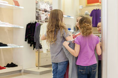 Two cute girls near a mirror try on clothes in a modern store Royalty Free Stock Image