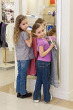 Two cute girls near a mirror try on clothes in a store Stock Photo