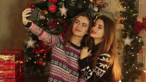 Two cute girls are photographed of a Christmas tree. Two cute young girls are photographed against the backdrop of a Christmas tree stock footage