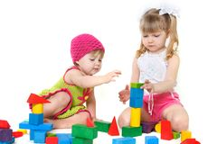 Two cute girls playing with building blocks. Over white royalty free stock images