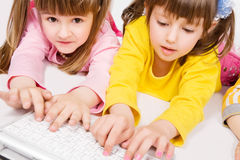 Two cute girls playing on laptop Royalty Free Stock Photo