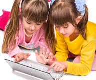 Two cute girls playing on laptop Stock Images