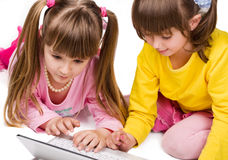 Two cute girls playing on laptop Stock Photo