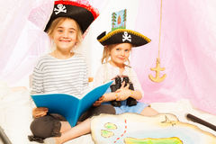 Two cute girls playing pirates, reading fairy-tale Royalty Free Stock Image
